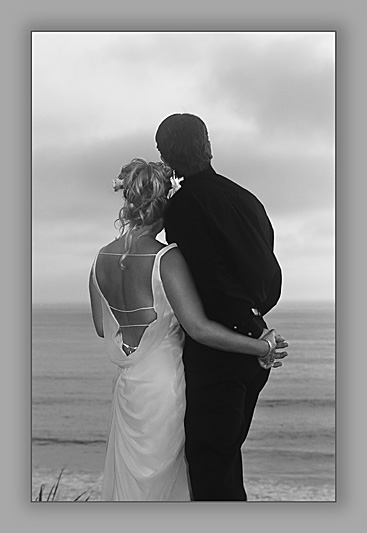 A newly married couple looking off toward the horizon at Del Mar, California