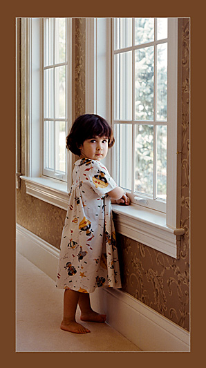 A young girl standing by a window looking back over her shoulder